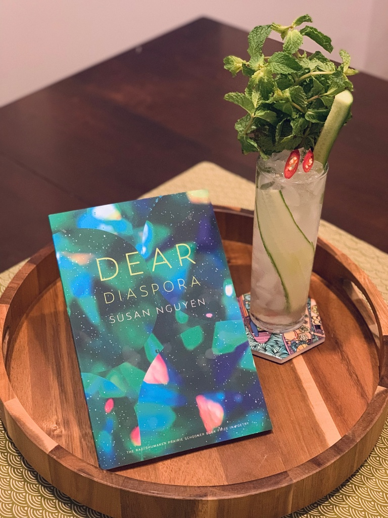 book titled Dear Diaspora by Susan Nguyen, propped next to a cocktail in a tall glass garnished with mint, cucumber, and Thai chili pepper