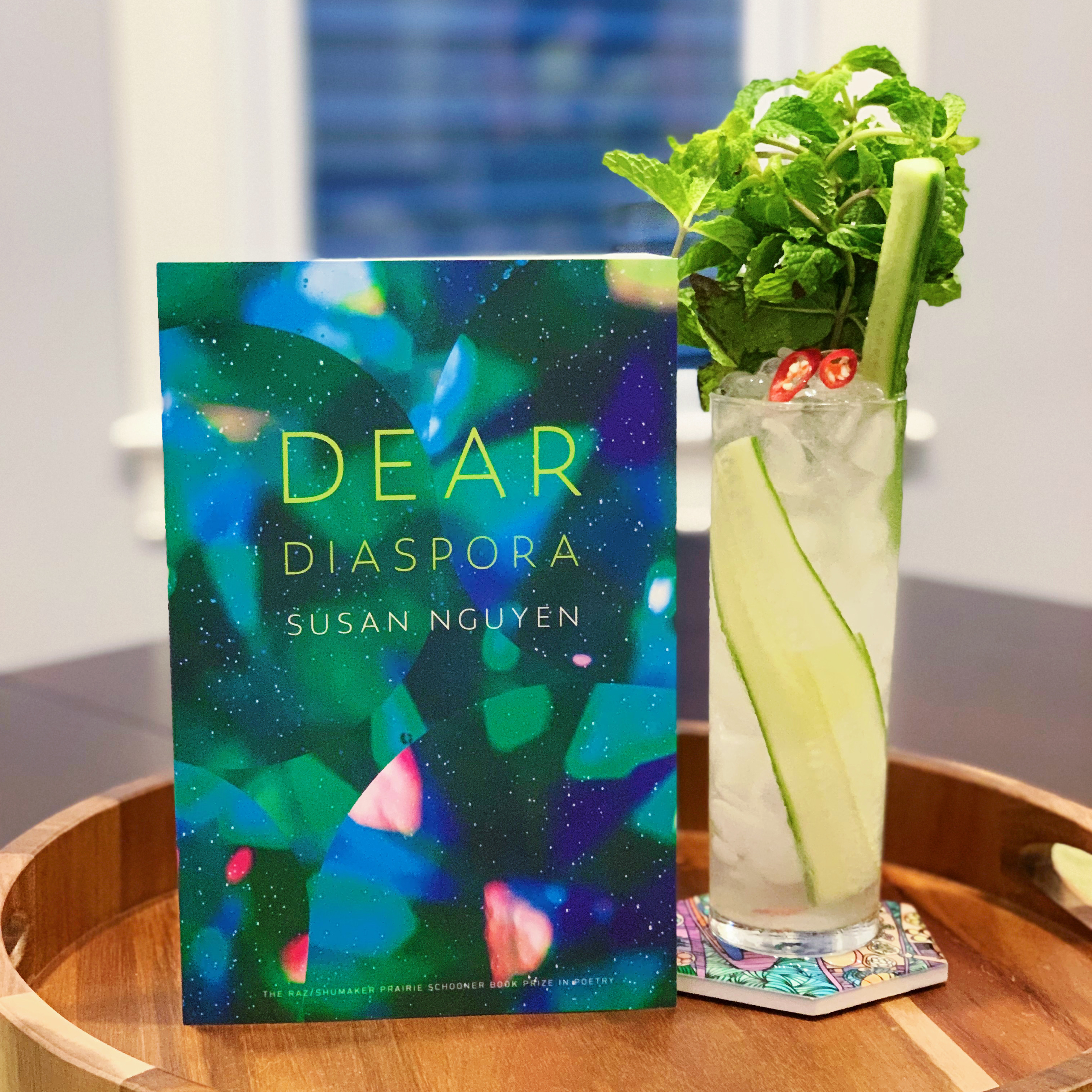 book titled Dear Diaspora, propped next to a cocktail in a tall glass garnished with mint, cucumber, and Thai chili pepper